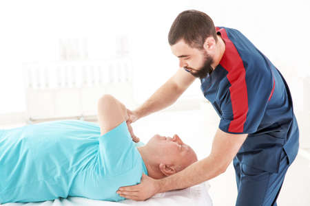 Young physiotherapist working with senior patient in clinic
