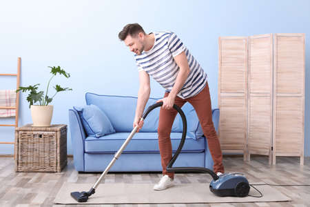 Mature man hoovering carpet with vacuum cleaner in living room