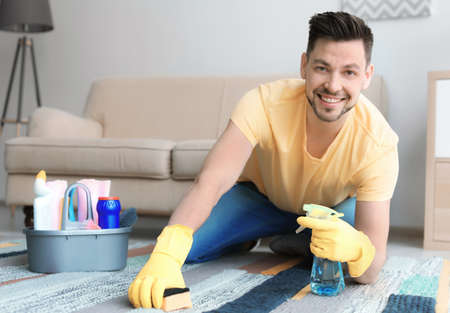 Mature man cleaning carpet at home