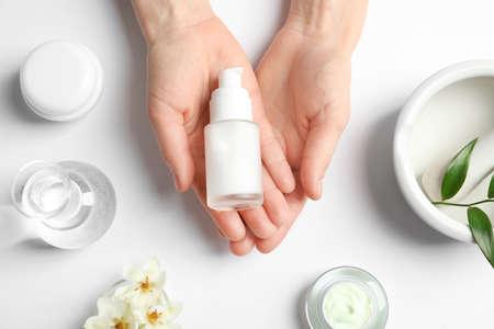 Mujer sosteniendo una botella de crema sobre la mesa con productos cosméticos Foto de archivo