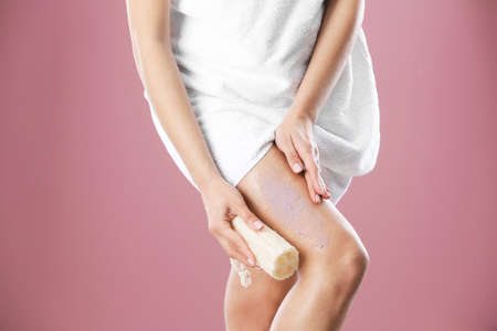 Young woman applying body scrub on leg against color background
