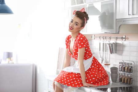 Casalinga giovane divertente che si siede sul bancone della cucina