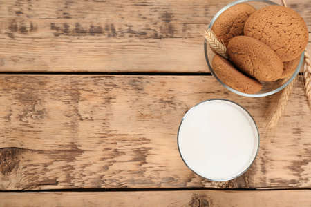 Glass of milk and oatmeal cookies on wooden table. Fresh dairy product