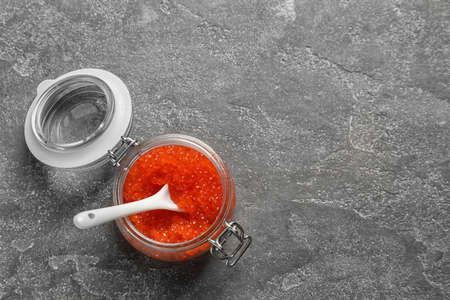 Jar with delicious red caviar on grey background Stock Photo