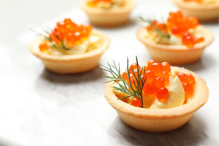 Delicious canapes with red caviar on table Stock Photo