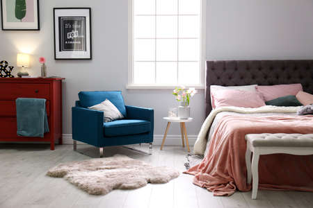Interior of light modern room with comfortable bed