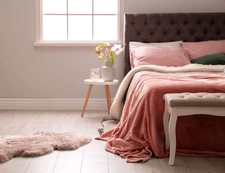 Comfortable bed in light modern room