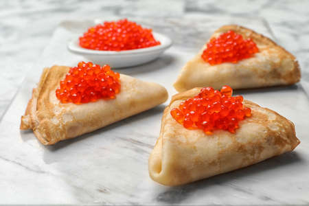 Thin pancakes with delicious red caviar on table