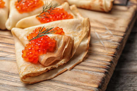 Thin pancakes with delicious red caviar on wooden board