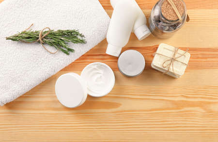 Flat lay composition with body care cosmetics on wooden background