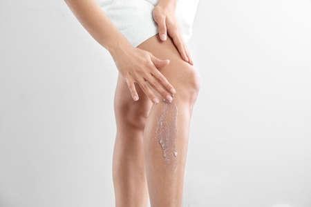 Young woman applying body scrub on leg against light background