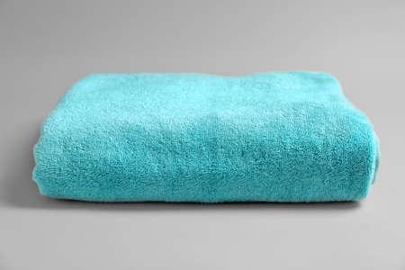 Soft bath towel on grey background