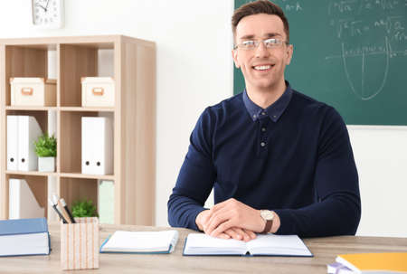 Young male teacher with book sitting at table in classroom
