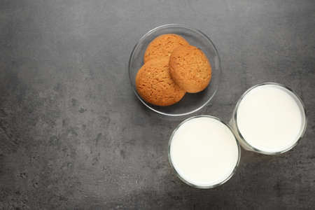 Glasses of milk and oatmeal cookies on table. Fresh dairy product