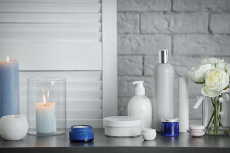 Body care cosmetics and burning candles on table Stock Photo