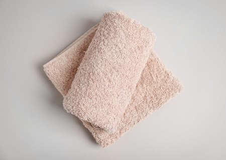 Soft bath towels on grey background, top view