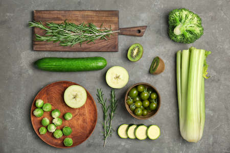 Flat lay composition with green vegetables and fruits on grey background. Food photography