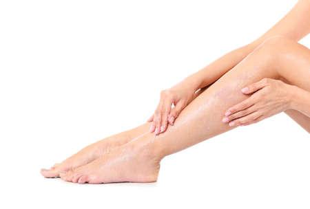 Young woman applying body scrub on leg against white background