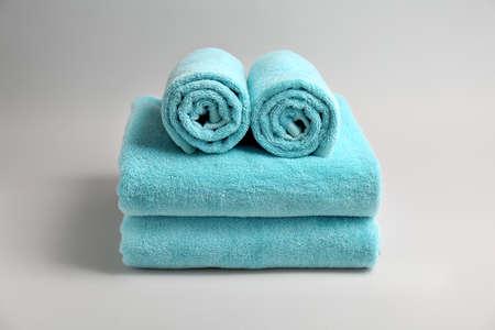 Soft bath towels on grey background Stock Photo