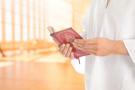 Young Muslim man reading Koran in mosque