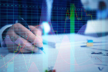 Graphs and businessman working with document at table on background. Financial trading concept