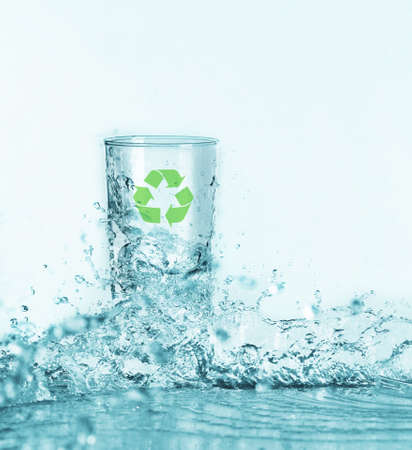 Glass with recycling symbol and water splash on light background. Save nature and environment