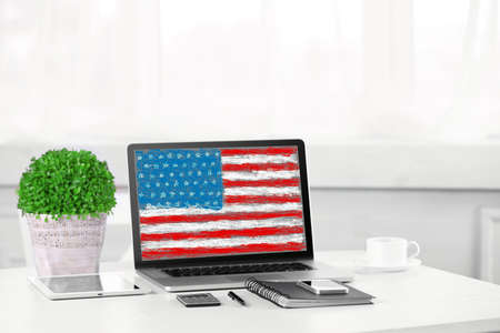 Modern workplace with laptop on table indoors. American flag on screen Stock Photo