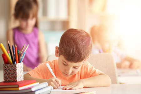 Little boy doing homework at table in classroom Banque d'images