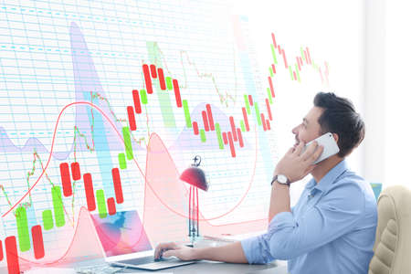 Financial trader talking by phone and looking at graphs on virtual screen in office. Forex concept