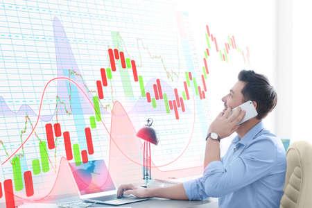 Trader financier parlant par téléphone et regardant des graphiques sur écran virtuel au bureau. Concept Forex