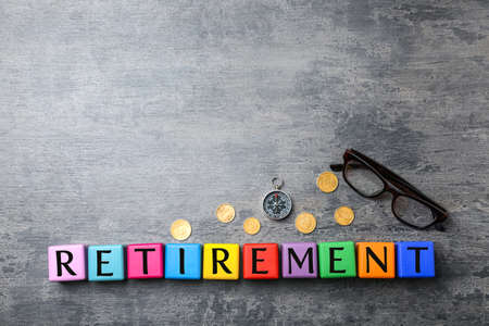 Cubes with word RETIREMENT, coins and compass on grey background. Pension concept Stock Photo
