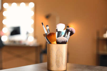 Holder with makeup brushes on table