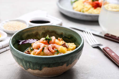 Bowl with tasty shrimps and grits on table
