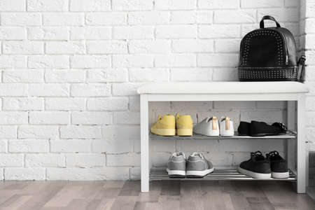 Collection of stylish shoes on rack storage near white brick wall
