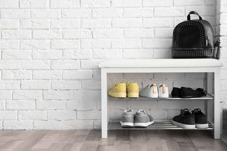 Sammlung von stilvollen Schuhen auf Gestellspeicher nahe weißer Backsteinmauer