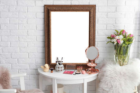 Table with beautiful mirror and cosmetics in modern makeup room Stock fotó