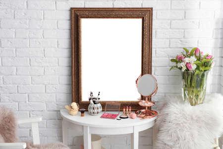 Tavolo con bellissimo specchio e cosmetici nella moderna sala trucco Archivio Fotografico