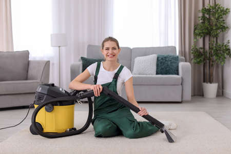 Female worker cleaning carpet with vacuum in living room Stock Photo