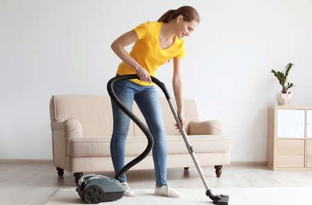 Mujer joven limpieza de alfombras con aspiradora en el salón Foto de archivo
