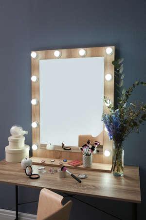 Mesa con hermoso espejo y cosméticos en la moderna sala de maquillaje Foto de archivo