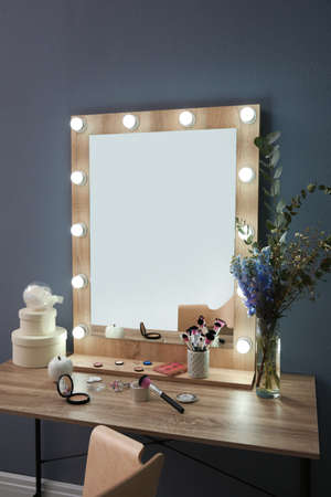 Table with beautiful mirror and cosmetics in modern makeup room Foto de archivo