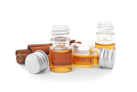 Bottles of cinnamon oil and sticks on white background 写真素材
