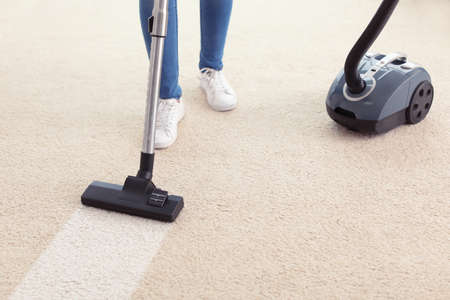 Woman hoovering carpet at home
