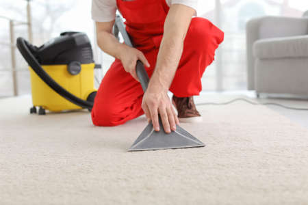 Male worker cleaning carpet with vacuum in living room