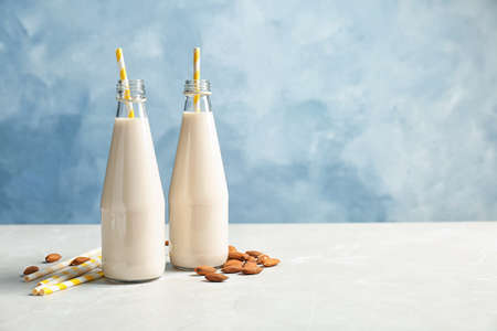 Bottles with almond milk and nuts on light table