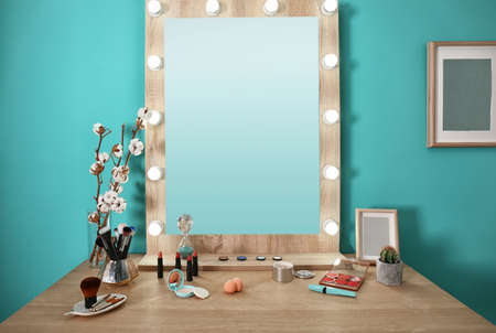 Decorative cosmetics and tools on dressing table near mirror in makeup room Stock Photo