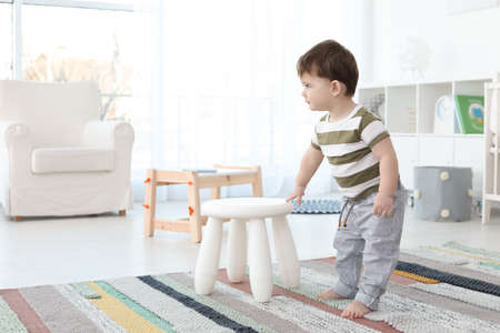 Cute baby holding on to stool at home.  Learning to walk