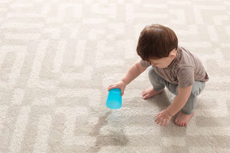 Baby sitting on carpet with empty glass Standard-Bild
