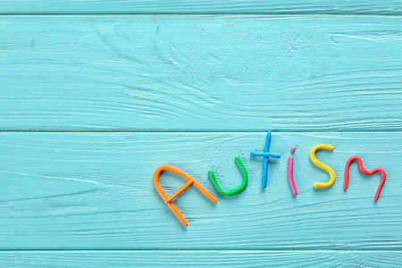 Word Autism made of plasticine on color wooden background