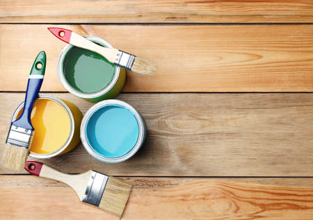 Brushes and paint cans on wooden background, flat lay